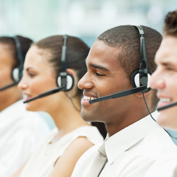Profile view of a young and diverse call center team wearing phone headsets. Horizontal shot.